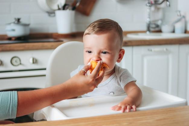 Uroczy mały chłopczyk jedzenia pierwszej żywności brzoskwini w kuchni.