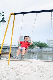 Uroczy mały chłopiec bawi się na huśtawce na świeżym powietrzu