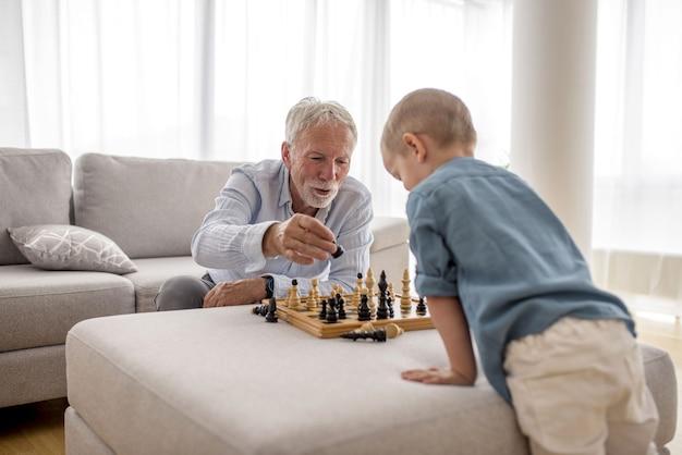 Uroczy mały chłopiec gra w szachy ze swoim dziadkiem