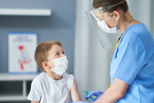 Uroczy mały chłopiec jest szczepiony w gabinecie lekarskim