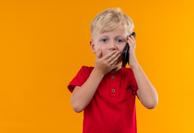 Uroczy mały chłopiec o blond włosach i niebieskich oczach ubrany w czerwoną koszulkę mówiący przez telefon komórkowy, patrząc zaskakująco z ręką na ustach