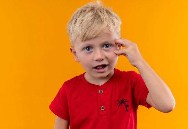 Uroczy mały chłopiec o blond włosach i niebieskich oczach ubrany w czerwoną koszulkę zaskakuje i trzyma rękę na głowie