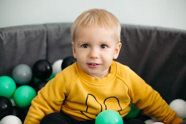 Uroczy mały chłopiec o blond włosach siedzi w basenie z piłeczkami z różnymi zielonymi, białymi i szarymi plastikowymi kulkami
