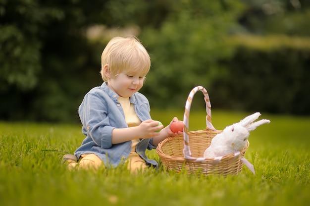 Uroczy mały chłopiec poluje na pisanki w parku na wielkanoc.