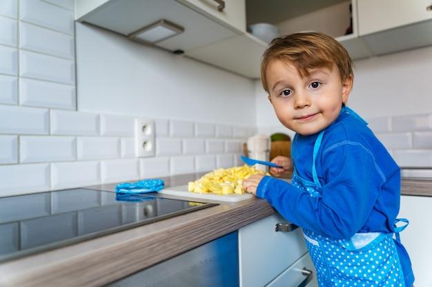 Uroczy mały chłopiec pomaga i piecze szarlotkę w domowej kuchni, wewnątrz