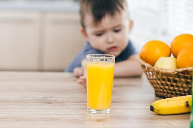 Uroczy mały chłopiec próbuje sięgnąć po sok z pomarańczy