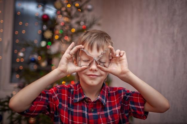 Uroczy mały chłopiec przygotowuje pierniki, piec ciastka w świątecznej kuchni.