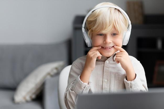 Uroczy mały chłopiec robi sesję logopedyczną online