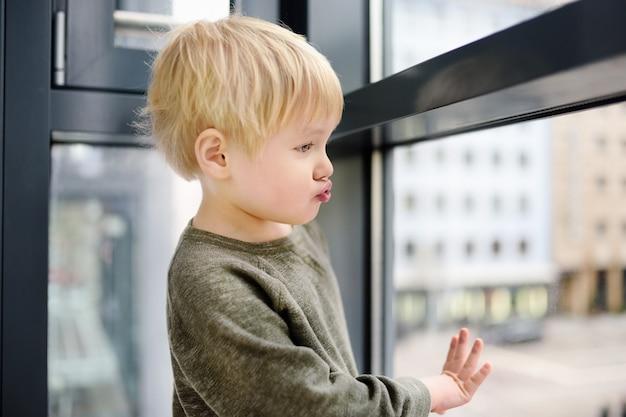 Uroczy mały chłopiec siedzi na oknie w pobliżu okna panoramicznego i patrząc na zewnątrz