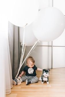 Uroczy mały chłopiec siedzi z dużymi białymi balonami, szczęśliwe dzieciństwo, gry dla dzieci