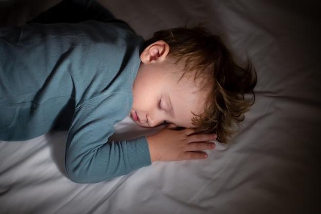 Uroczy mały chłopiec śpi w swoim łóżku w ciemności w domu. pora snu. dziecko śni i odpoczywa w nocy.