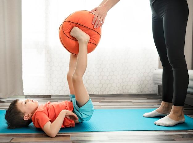 Uroczy mały chłopiec trenuje z mamą w domu