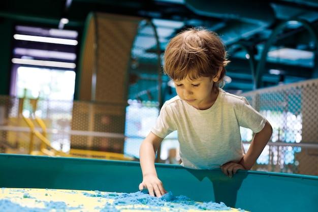 Uroczy mały chłopiec w centrum gier edukacyjnych dla dzieci zapoznaje się z piaskiem kinetycznym. rozwój umiejętności motorycznych. nowoczesne gry edukacyjne. kreatywność i samorealizacja.