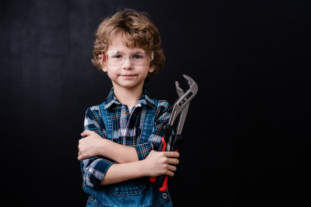 Uroczy mały chłopiec w odzieży roboczej i okularach ochronnych, trzymając handtool, stojąc przed czarną przestrzenią