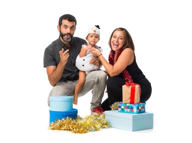 Uroczy mały dziecko z jego rodzicami przy bożymi narodzeniami bawi się na odosobnionym białym tle