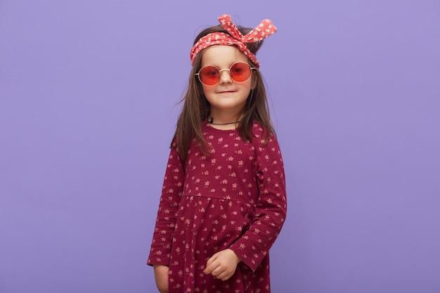 Uroczy mały hipster modna dziewczyna ubrana w bordową sukienkę