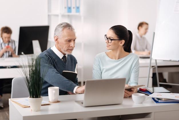 Uroczy mężczyzna ubrany w niebieski kardigan za pomocą laptopa, pokazując nowe zmiany w pracy
