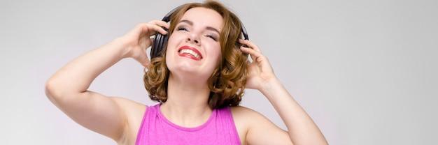 Uroczy młoda dziewczyna w różowej sukience na szarym tle. młoda dziewczyna z hełmofonów ono uśmiecha się
