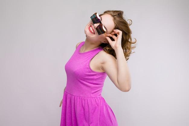 Uroczy młoda dziewczyna w różowej sukience na szarym tle. rozochocona dziewczyna w kwadratowych szkłach. dziewczyna poprawia okulary