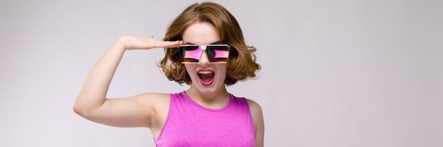 Uroczy młoda dziewczyna w różowej sukience na szarym tle. rozochocona dziewczyna w kwadratowych szkłach. dziewczyna przyłożyła rękę do głowy