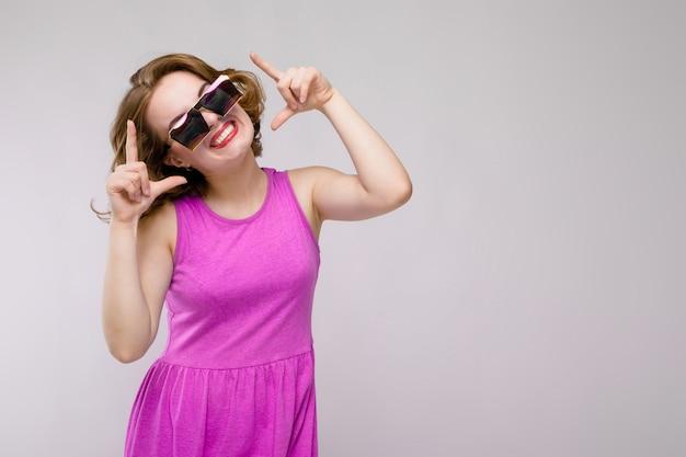 Uroczy młoda dziewczyna w różowej sukience na szarym tle. rozochocona dziewczyna w kwadratowych szkłach. dziewczyna wskazuje palcami na górę