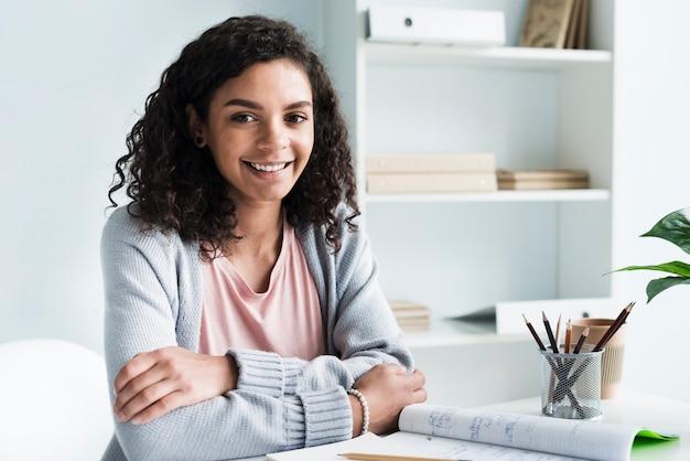 Uroczy młoda kobieta siedzi w miejscu pracy