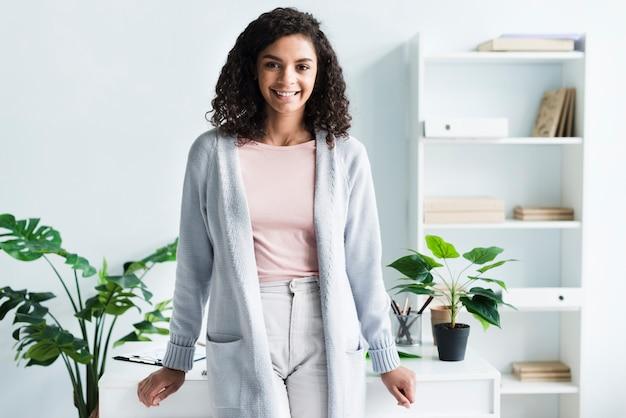 Uroczy młoda kobieta stojąca w miejscu pracy