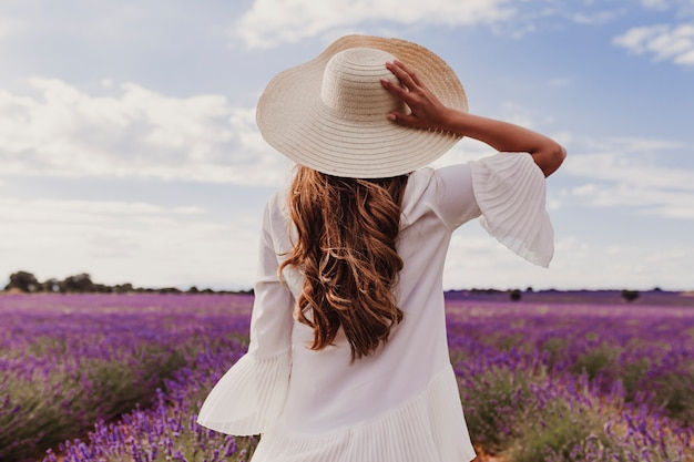 Uroczy młoda kobieta w kapeluszu i białej sukni w fioletowym polu lawendy o zachodzie słońca