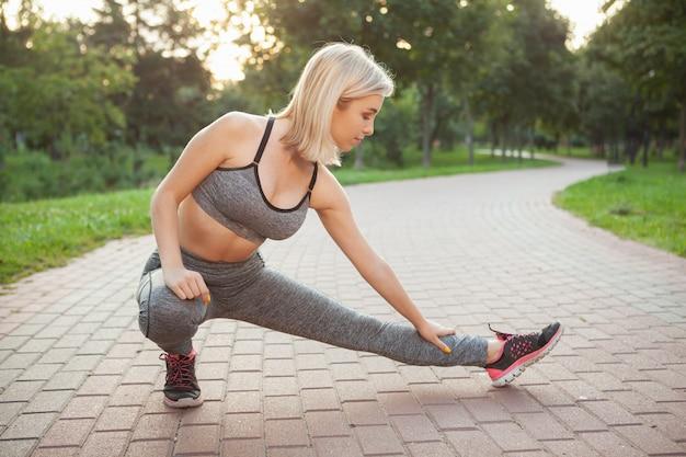 Uroczy młoda sportsmenka ćwiczenia w parku w godzinach porannych