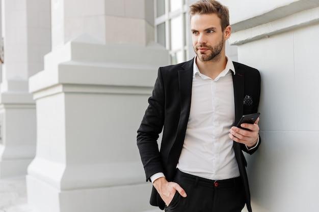 Uroczy młody biznesmen w garniturze stojący w mieście, korzystający z telefonu komórkowego