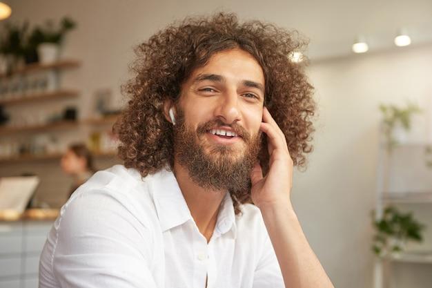 Uroczy młody brodaty mężczyzna z długimi kręconymi włosami wyglądający wesoło, siedzący w kawiarni i słuchający muzyki w słuchawkach, uśmiechający się szeroko i dotykający policzka