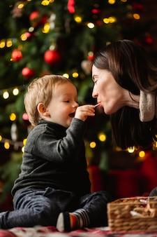 Uroczy młody chłopak bawi się zabawkami świątecznymi