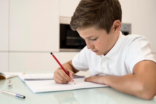 Uroczy młody chłopak odrabia lekcje