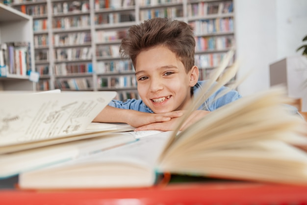 Uroczy młody chłopak uśmiecha się, odpoczynek w bibliotece po przeczytaniu i studiowaniu
