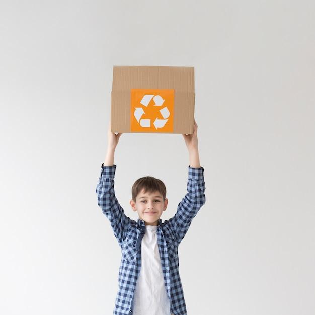 Uroczy młody chłopiec mienie przetwarza pudełko