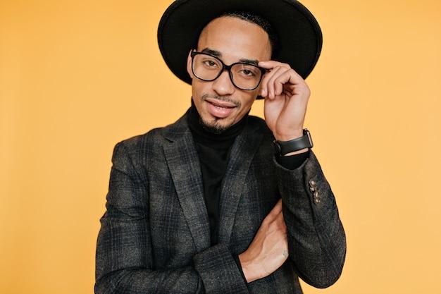Uroczy młody człowiek z brązową skórą pozuje w eleganckim zegarku. poważny afrykański facet w modnym garniturze stojący na żółtej ścianie.