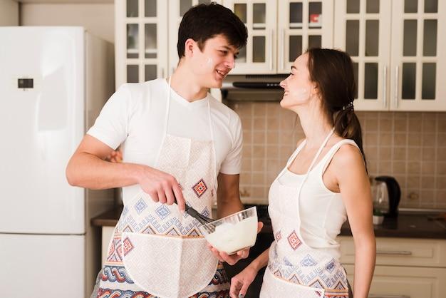 Uroczy młody mężczyzna i kobieta gotuje razem