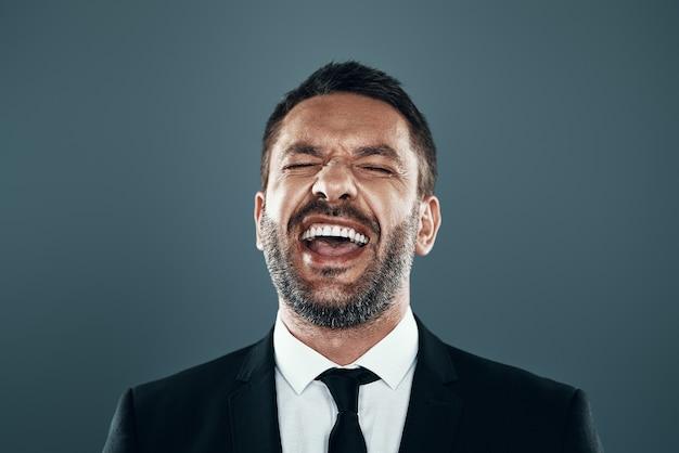 Uroczy młody mężczyzna w pełnym garniturze, śmiejąc się, stojąc na szarym tle