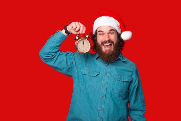 Uroczy młody mężczyzna z brodą w kapeluszu świętego mikołaja trzymający budzik na czerwonym tle