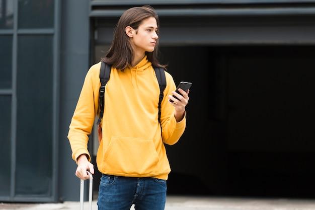 Uroczy młody podróżnik trzyma jego telefon