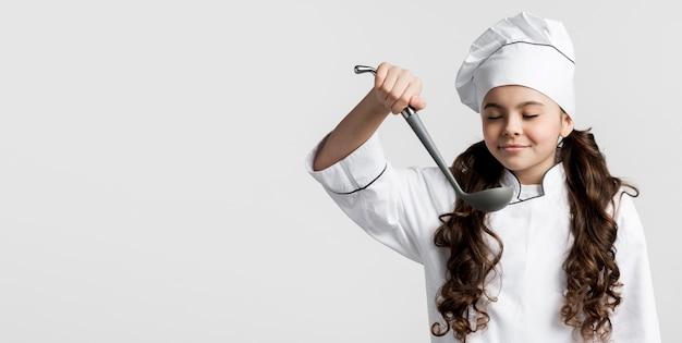 Uroczy młody szef kuchni trzyma zupną kopyść