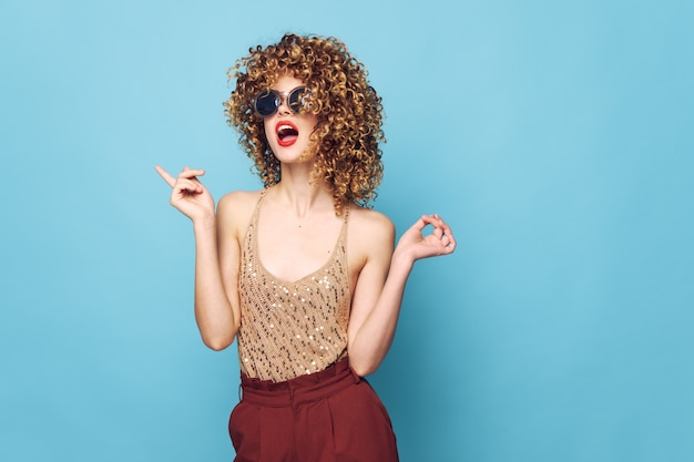 Uroczy model kręcone włosy moda ubrania czerwone usta czerwone spodnie na białym tle