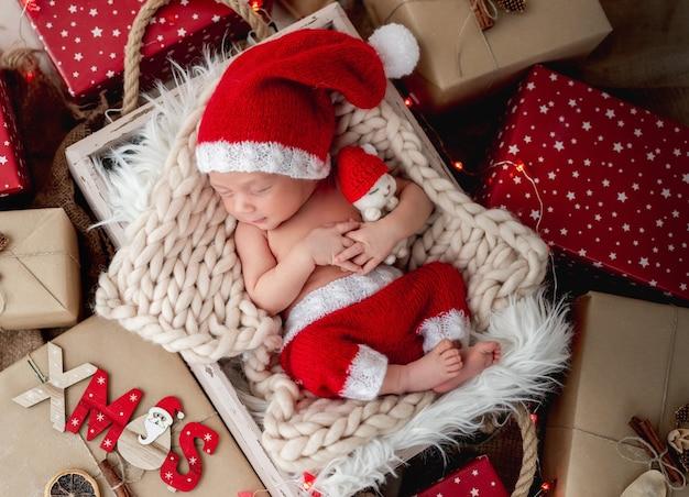 Uroczy noworodek śpiący między prezentami świątecznymi