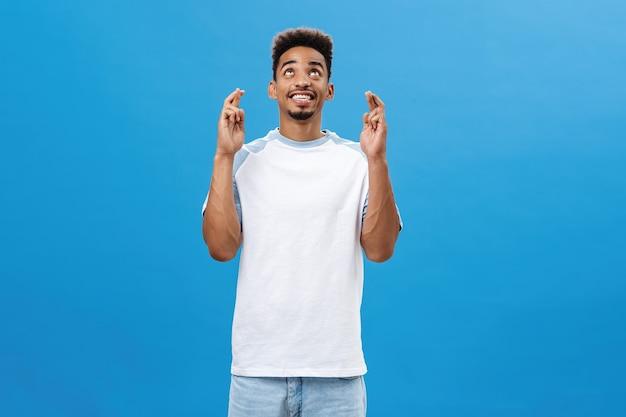 Uroczy optymistyczny afroamerykanin proszący bóg pomóż mu czeka zadowolona i szczęśliwa ciemnoskóra j...