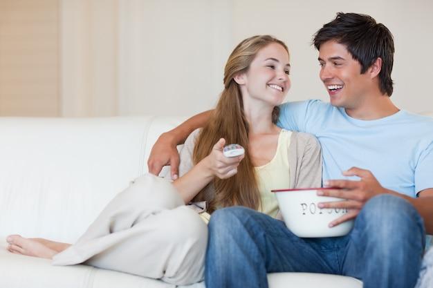 Uroczy para oglądania telewizji podczas jedzenia popcornu