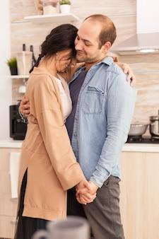 Uroczy para taniec w kuchni. szczęśliwa młoda rodzina. miłość żony i męża, romans, czuła chwila, zabawa i szczęście w domu, wspólna muzyka wesoła i uśmiechnięta