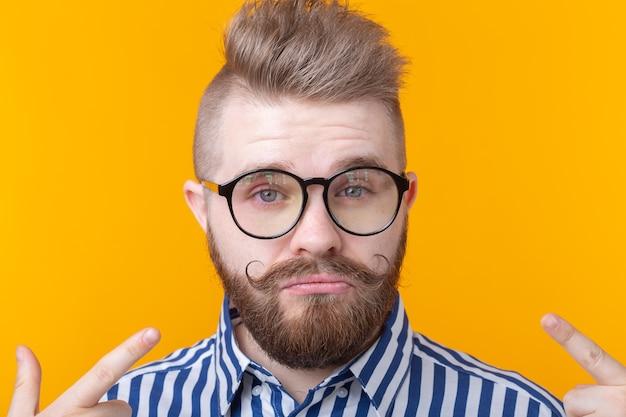 Uroczy pewny siebie hipster młody mężczyzna w okularach i brodzie pokazuje się na żółtej ścianie. miejsce na reklamę