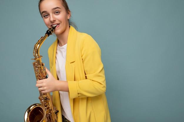 Uroczy pozytywny uśmiechający się brunetka żeński nastolatek sobie modny żółty płaszcz stojący na białym tle nad niebieskim tle ściany gry na saksofonie patrząc na kamery. skopiuj miejsce