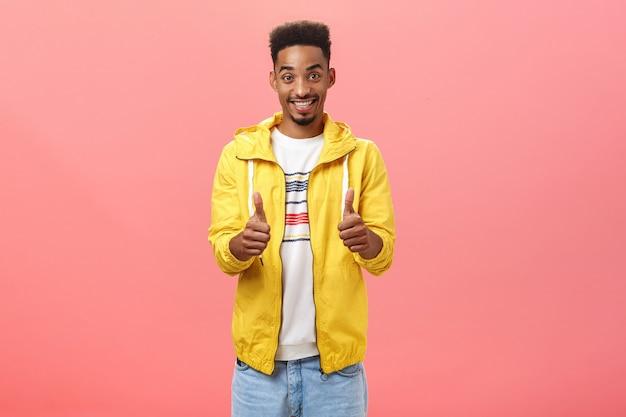 Uroczy przyjacielski chłopak wspierający i optymistyczny, podający kciuki w górę i szeroko uśmiechający się, wzmacniając pewność siebie kolegi aprobującego jego pomysł, pozującego zadowolonego i zachwyconego na różowej ścianie.