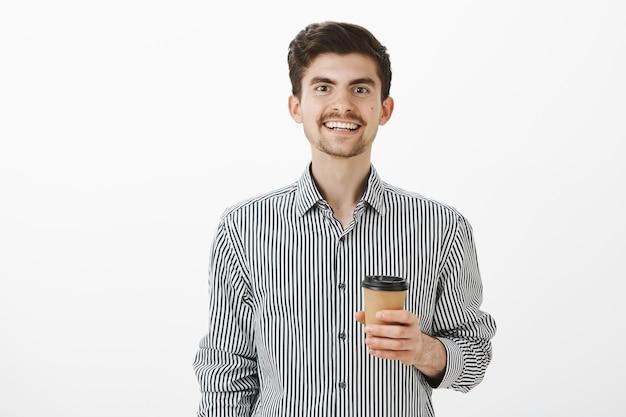 Uroczy przyjazny facet przyniósł kawę współpracownikowi, którego lubi. portret uroczego chłopaka w koszuli, uśmiechającego się szeroko i trzymającego filiżankę herbaty, rozmawiającego swobodnie ze współpracownikiem w biurze nad szarą ścianą